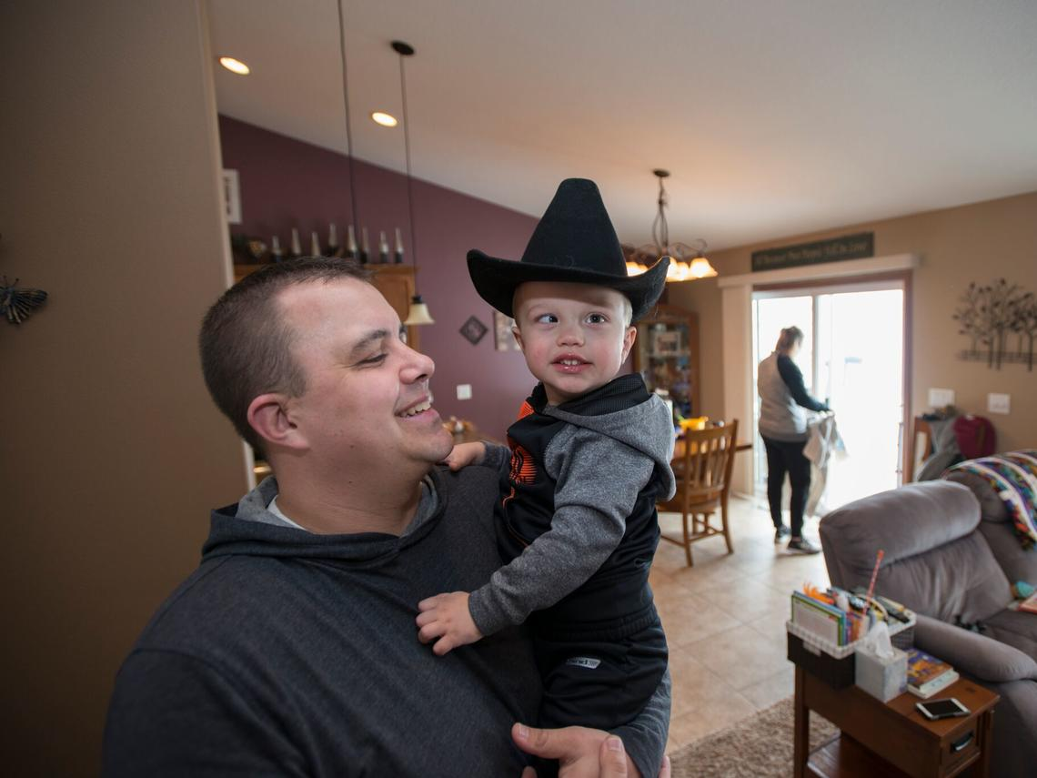Father holding son wearing cowboy hat