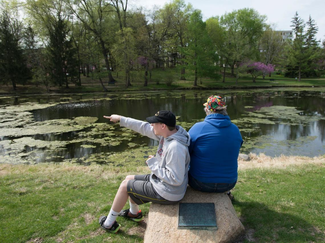 Man and father sitting by the lake