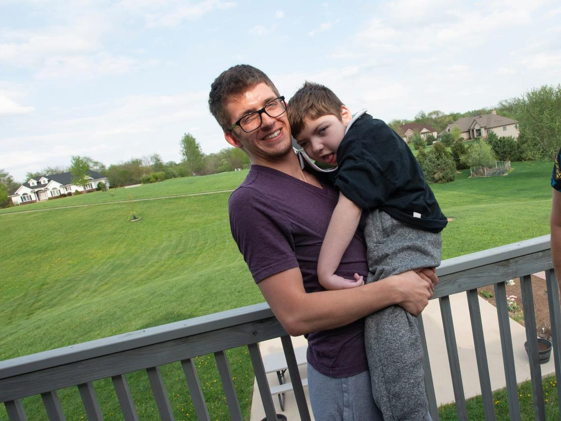 Young man holding brother in back yard