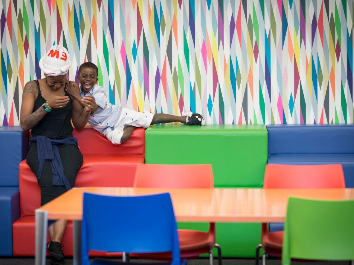 Mom and young boy laughing in front of colorful wall