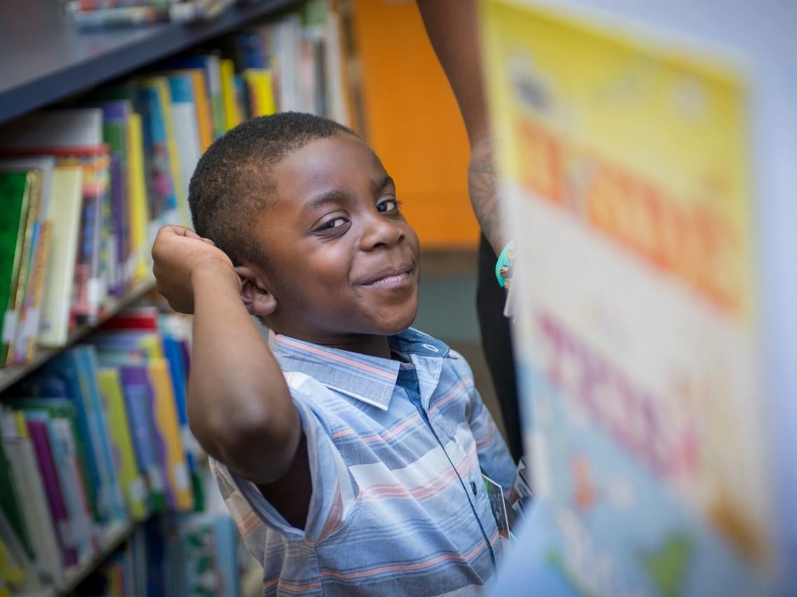 Boy smiling at the camera in library