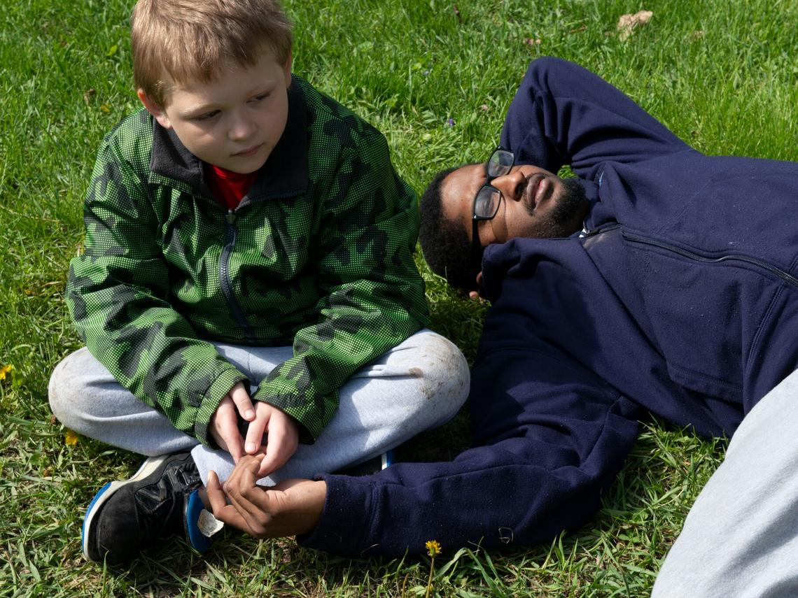 Boy sitting on the grass with his father