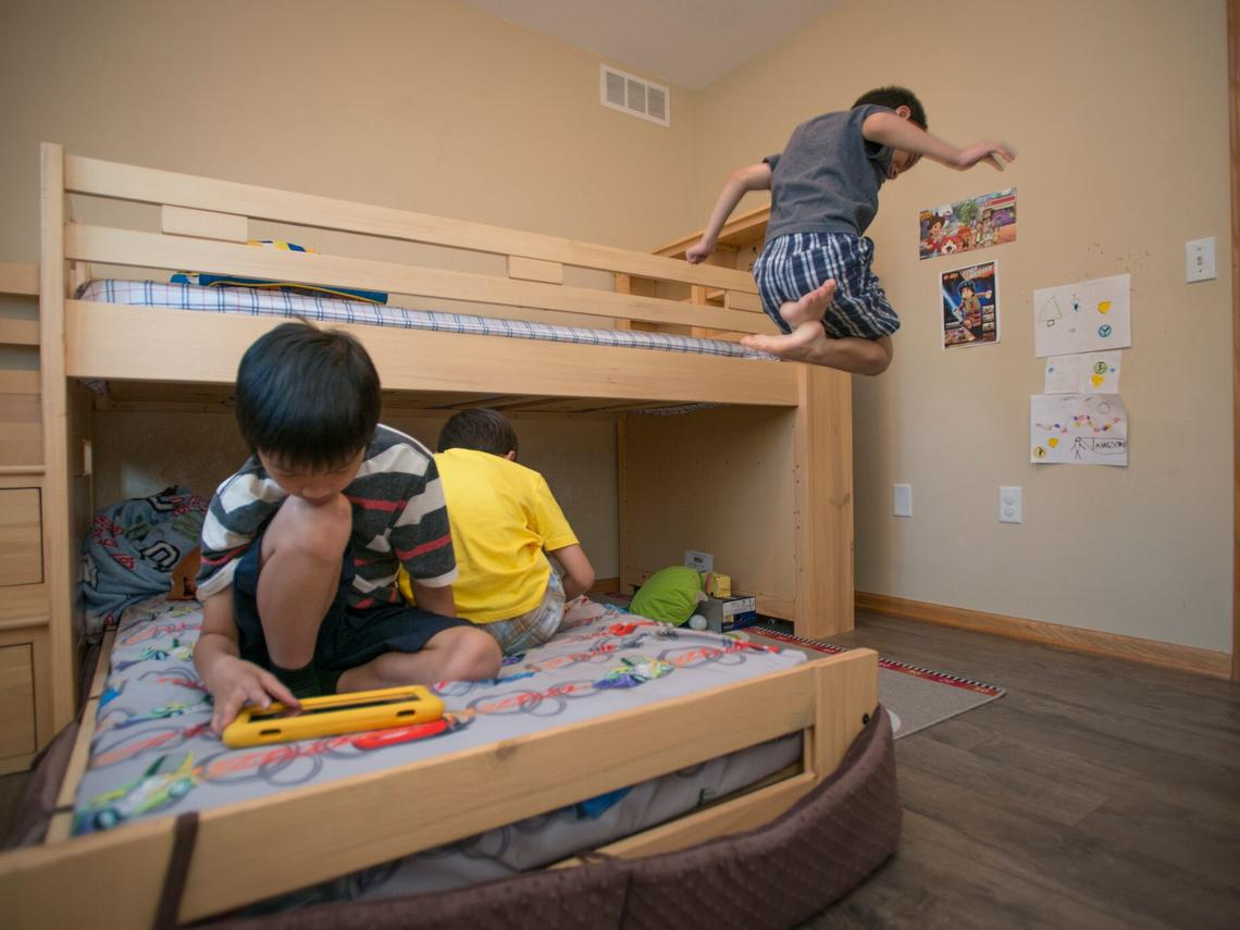 Boy jumping off bunk bed